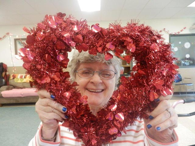 A happy Day Habilitation attendee holding a Valentine they made