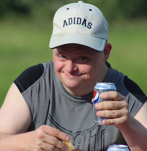 Happy male at a picnic holding a soda